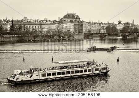 PRAGUE CZECH REPUBLIC - FEBRUARY 02 2014: House of old Prague and Vltava river. Sepia. Stylized film. Large grains. Prague is the capital and largest city of the Czech Republic