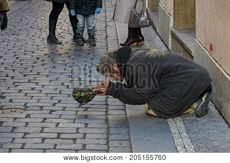 PRAGUE CZECH REPUBLIC - FEBRUARY 03 2014: Beggar kneeling begging in the Old Town.