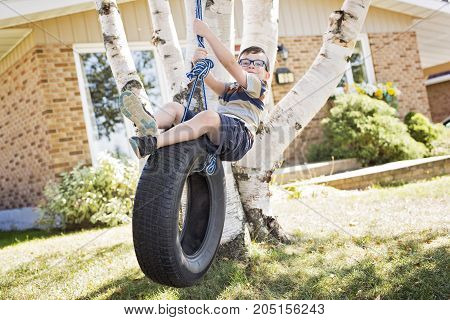 A boy standing on tire swing outside