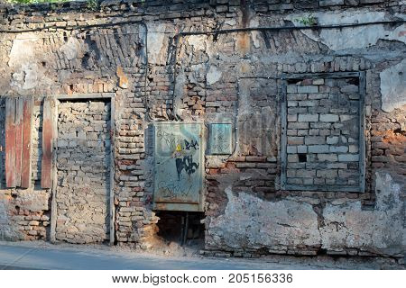 An old stone house with boarded up doors and windows brick
