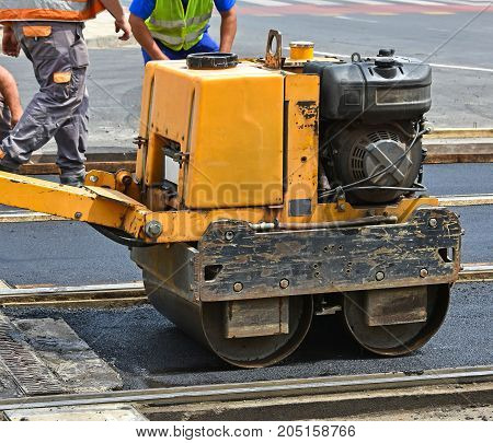 Road construction with steam roller in the city