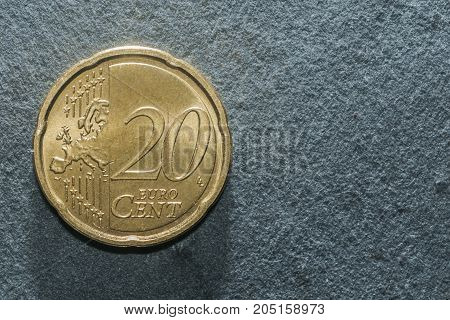 A 20 cent euro coin on a grey background