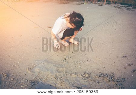 Charming Young Girl Is Looking For Sea Animals On The Beach