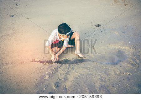 Asian Child Has Fun Digging In The Sand. Young Boy Enjoying On Beach.
