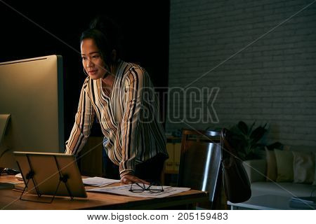 Indonesian business woman reading information on computer screen in dark office
