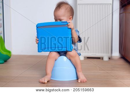 Cute little Asian 18 months / 1 year old toddler baby boy child is on blue potty while playing with digital tablet at home potty training & internet addiction concept - Selective focus at tablet