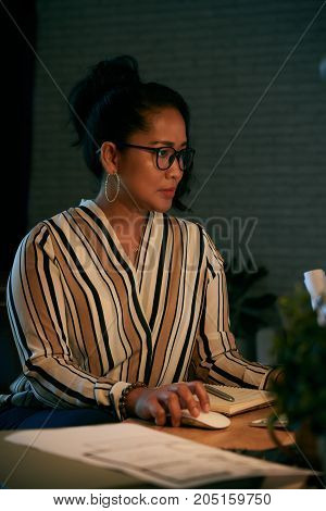 Indonesian business lady concentrated on work in her office