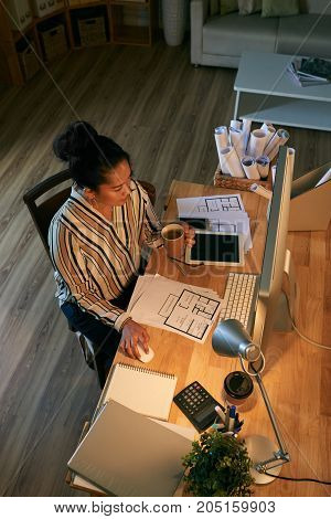 Indonesian real estate agent working on computer in her dark office