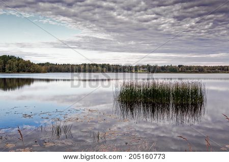 Autumn at the lake Piipsjarvi in the Northern Finland. The dark clouds are reflecting on the still surface of the water.