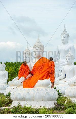 Sa Kaeo Thailand - July 14 2013: Monks dressing one of White Buddha Image with robes in Buddha Park of Sa Kaeo Thailand