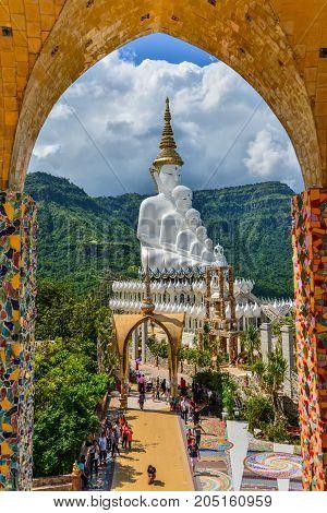 Phetchabun Thailand - June 28 2015: Buddhist tourists sightseeing beautiful white five Buddha Images at Phasornkaew Buddhist temple in Phetchabun Thailand