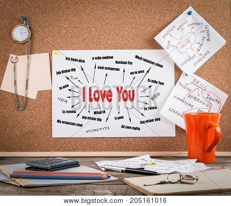 I love you Concept. Chart with text in different languages. Communication and love background. Wooden office desk with a big mess.