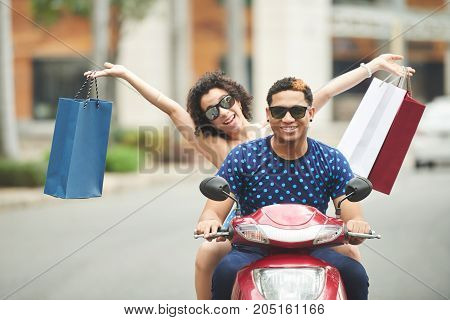 Happy couple riding on scooter with many bags after shopping