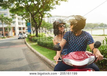 Joyful Cuban couple riding on moped in summer city