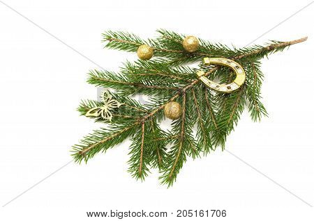 Fir tree branches with Christmas ball and toy butterfly and horseshoe isolated on white background. Christmas decoration.