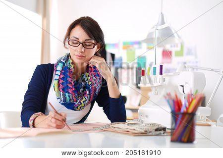 Beautiful fashion designer sitting at the desk in studio