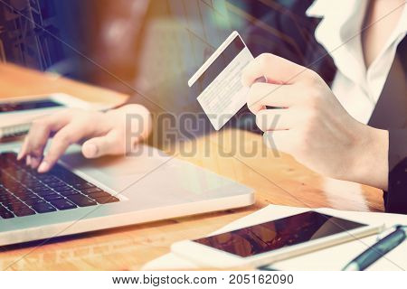 female hand of business woman holding credit card making purchase online with window reflection and lens flare effect good for business ecommerce concept