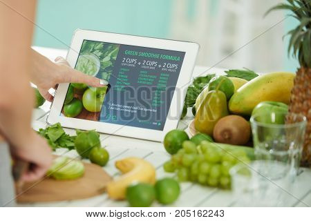Close-up image of woman reading green smoothie formula on tablet screen
