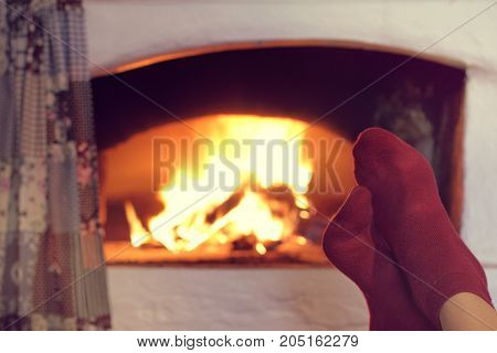 man warms his feet in red socks next to a burning fireplace / warming atmosphere of home comfort