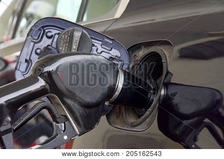 gas pump in tank of dark car pumping fuel