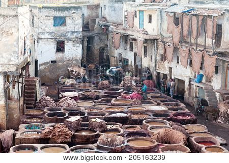 FEZ, MOROCCO - JANUARY 4, 2014: Men working hard in the Chouara tanneries. Tannery souk of weavers is the most visited part of the 2000 years old city.