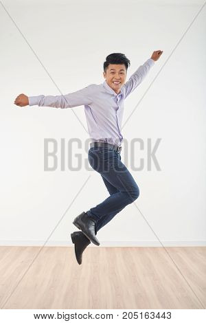 Jumping happy excited Vietnamese young handsome man