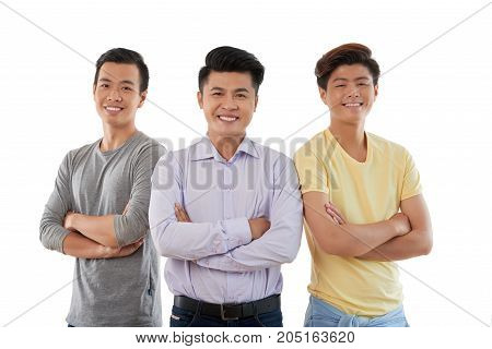 Three male friends standing with their arms crossed
