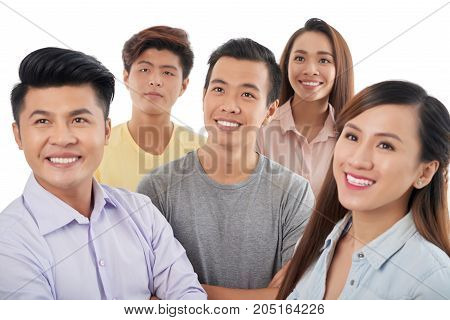 Group of smiling Vietnamese young people looking-up at something interesting