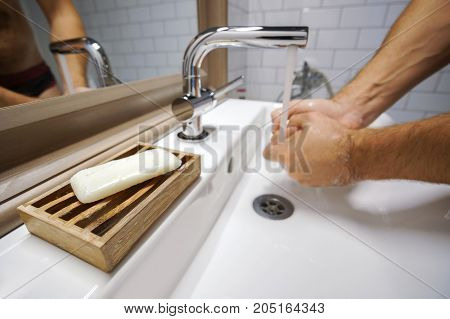 purity and health. soap for washing hands in the bathroom on the background of a person near the sink in the bathroom.
