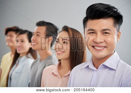 Portrait of smiling young Vietnamese businessman, his colleagues are in the background