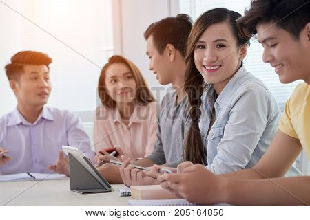 Pretty smiling young woman attending meeting with colleagues