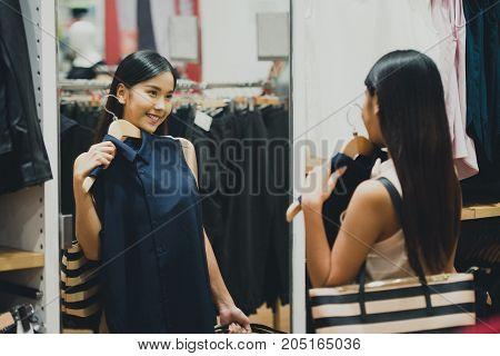 Woman shopping choosing dresses looking in mirror uncertain. Beautiful young asian shopper in clothing store.