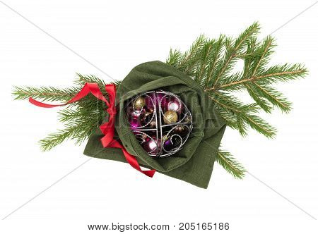Christmas present bag with red ribbon bow with christmas balls laying in fir tree branches isolated on white background. Christmas decoration.