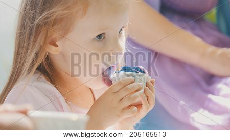 Cute blonde girl eating cupcake outdoor with family, close up