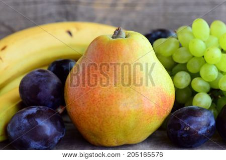 Fresh colorful fruits assortment. Fresh raw pear, grapes, blue plums, bananas on a wooden table. Closeup