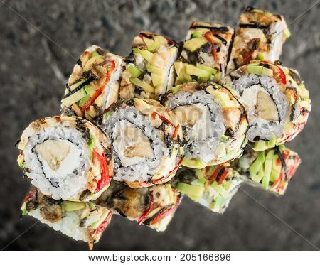 Roll wrapped with eel, avocado with banana over concrete background