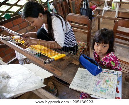Mother Works Loom While Child Does Homework