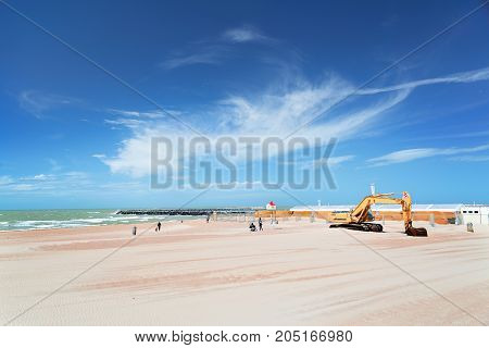 The beach on the North Sea in Ostende Belgium. The blue sky with picturesque clouds several people in the distance and the excavator which is partially brought by sand