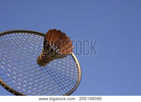 Badminton with golden racket and shuttlecock sky blue.