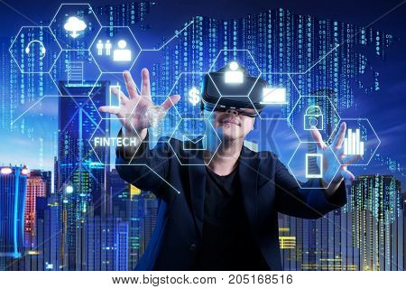Businessman touching fintech infographic icon on digital virtual screen with both hands. Hi-tech business concept .