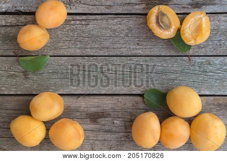 Ripe orange apricots are arranged on the left and right of grey wooden background