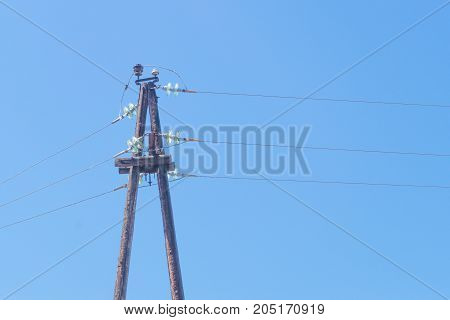 Electrical post by the road against clean blue sky