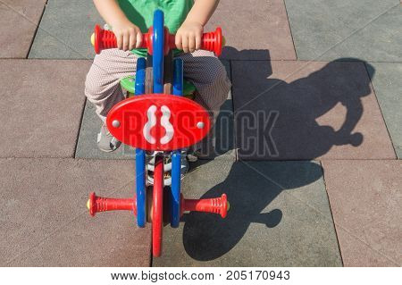 Little boy sways on the toy swing motorcycle in the children playground