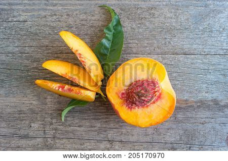 One ripe peache with slices and green leaf on the wooden background