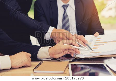 Businessmen partner teamwork group together holding pen point graph consult for successful project complete with tablet and notebook