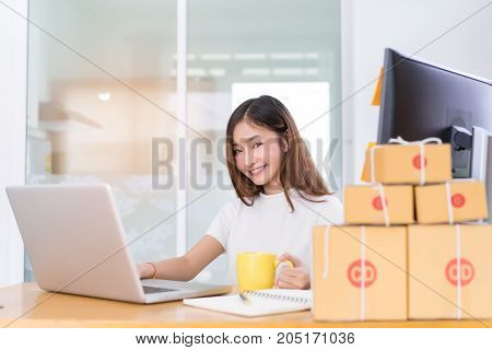 Young asian woman freelancer small business private working at home office with laptop note coffee packaging delivery online market on purchase orders to customer.