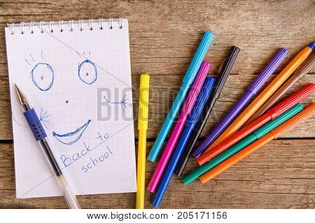 Open white notepad with drawing and inscription BACK TO SCHOOL with colorful felt-tip pens and ball pens on the table