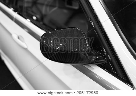 Carbon Right side Car mirror with reflection of a modern car. Car exterior details. Black and white