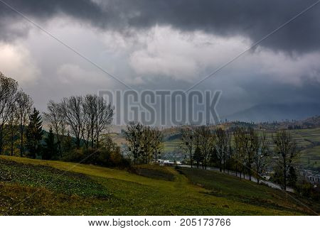 rural fields on serpentine in bad weather. mountainous countryside with trees in autumn stormy evening