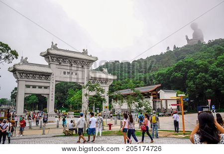 HONG KONG - MAY 31: Tourists at the gate to Po Lin Monastery with Tian Tan Buddha statue up on the hill in background, Ngong Ping Village, Lantau Island, Hong Kong